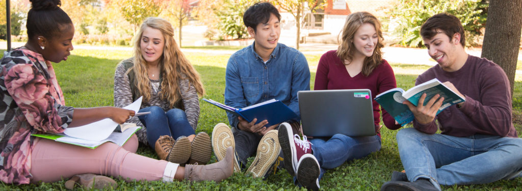 Diverse group of students study together outdo要么s.